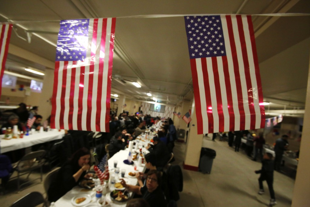 People sit down for a meal during a celebration for new U.S. citizens at St. Rita of Cascia Catholic Church in Chicago on March 30, 2019. The neighbor...
