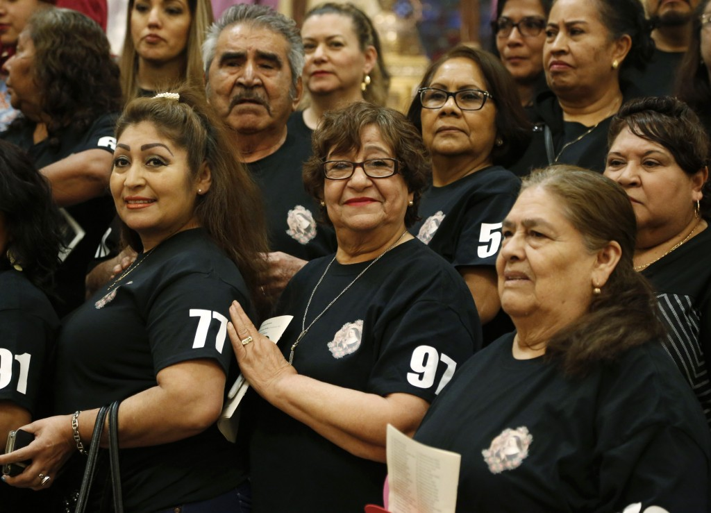 New U.S. citizens, many of them originally from Mexico, stand on the altar for a photo at St. Rita of Cascia Catholic Church in Chicago on March 30, 2...
