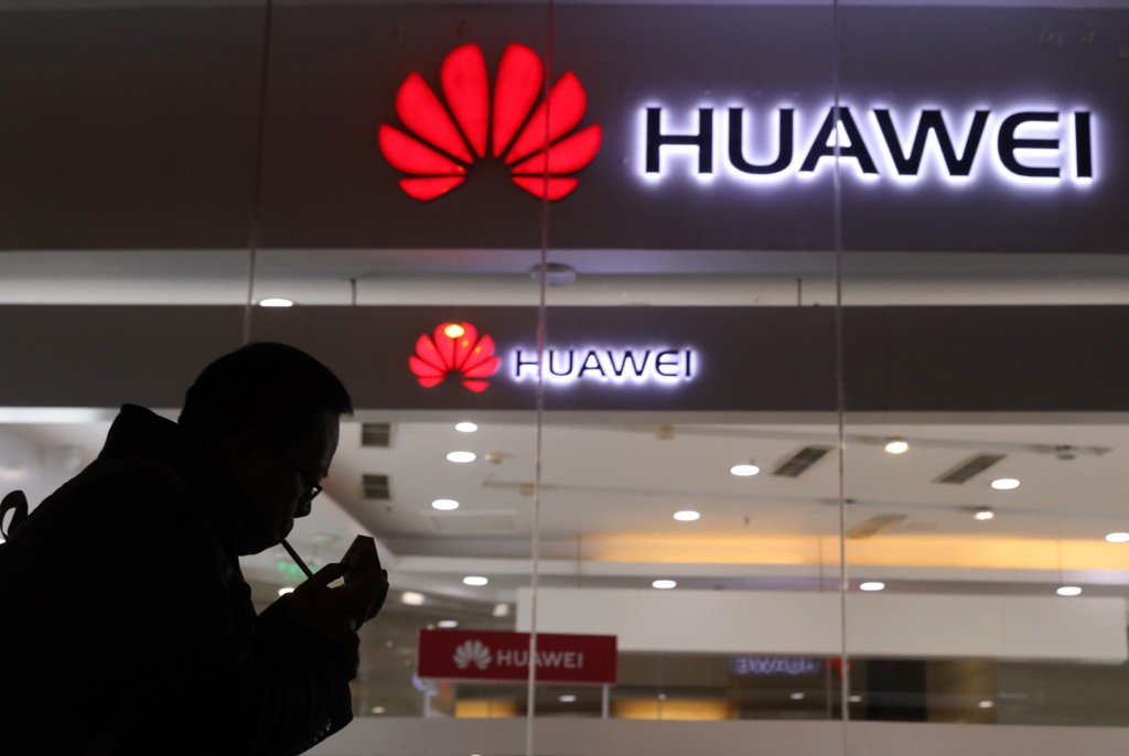 Man lights cigarette outside Huawei retail shop in Beijing.