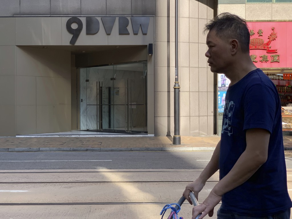 A worker walks past a building listed as the address of China Innovation Investment Limited in Hong Kong, Saturday, Nov. 23, 2019. Australia's Treasur...