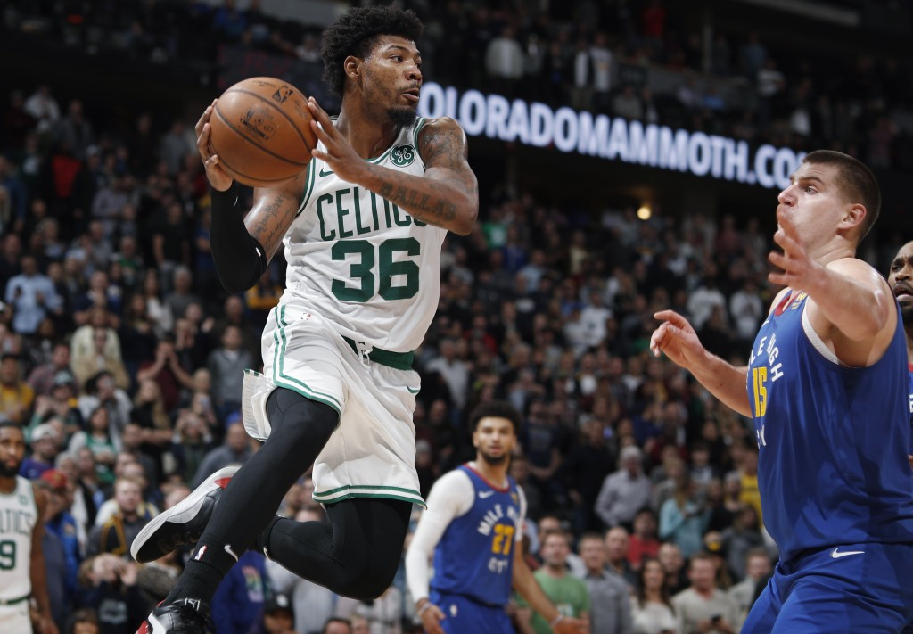 Boston Celtics guard Marcus Smart pulls in a rebound as Denver Nuggets center Nikola Jokic defends during the second half of an NBA basketball game Fr...