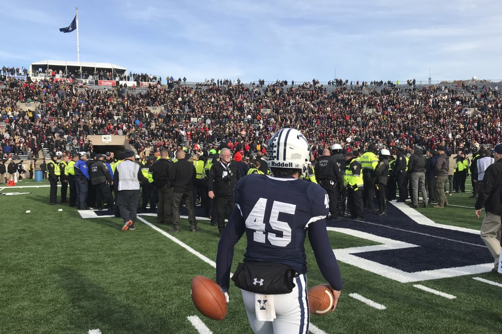 Yale punter Jack Bosman watches as demonstrators stage a protest on the field at the Yale Bowl disrupting the start of the second half of an NCAA coll...