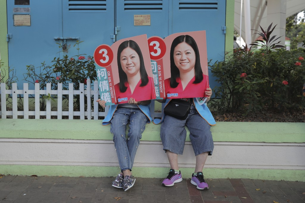 In this Sunday, Nov. 24, 2019, file photo, supporters of pro China candidate Or Sin-yi Windy hold her promotional placards in Hong Kong. Long lines sn...