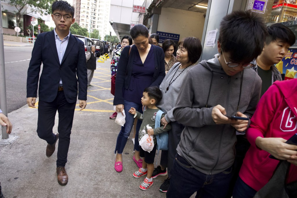 Pro-democracy activist Joshua Wong walks past people lined up to vote outside of a polling place in Hong Kong, Sunday, Nov. 24, 2019. Voting was under...