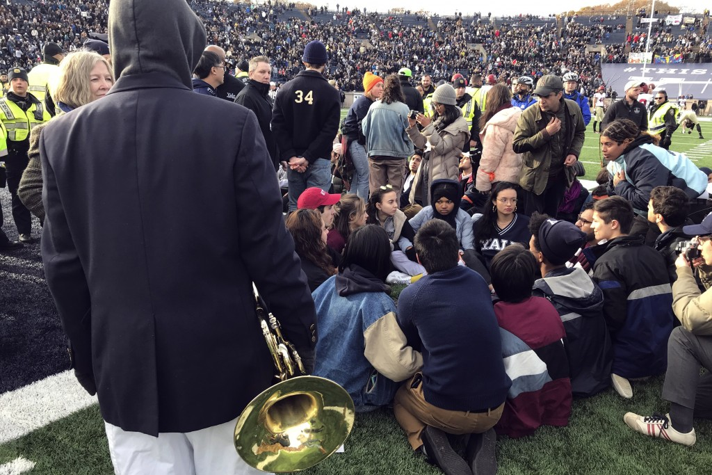 Demonstrators stage a protest on the field at the Yale Bowl disrupting the start of the second half of an NCAA college football game between Harvard a...