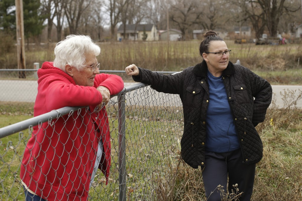 In this photo taken Monday, Nov. 18, 2019, Tammy Kilgore, right, talks to her neighbor Betty Cazzell after Kilgore's home was demolished in Mosby, Mo....
