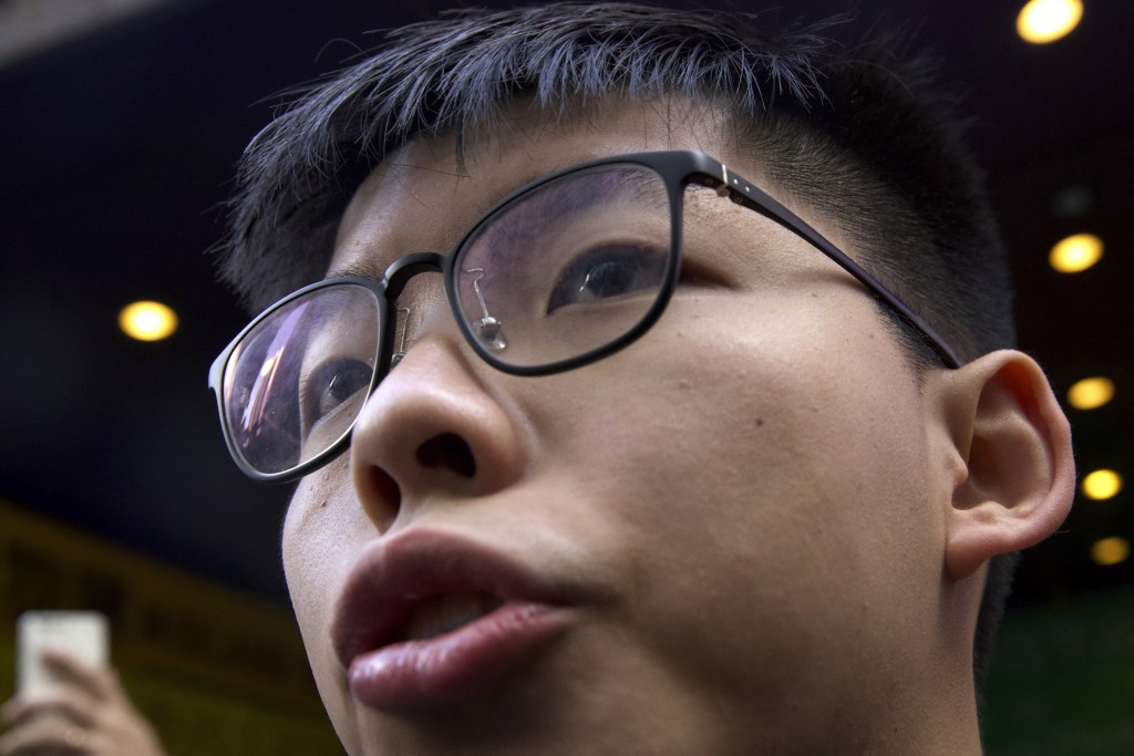 Pro-democracy activist Joshua Wong speaks to journalists outside of a polling place in Hong Kong, Sunday, Nov. 24, 2019. Voting was underway Sunday in...