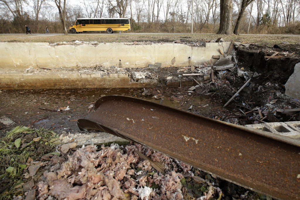 In this photo taken Monday, Nov. 18, 2019, a school bus drops students in front of a recently demolished home in Mosby, Mo. The home is one of dozens ...