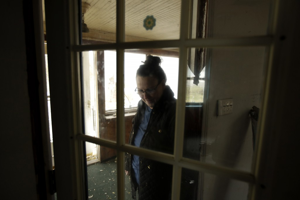 In this photo taken Monday, Nov. 18, 2019, Tammy Kilgore walks through the front door of her home for the final time before it was demolished as part ...