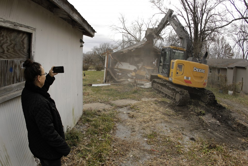 In this photo taken Monday, Nov. 18, 2019, Tammy Kilgore watches while her former home is demolished as part of a voluntary buyout in flood-prone Mosb...