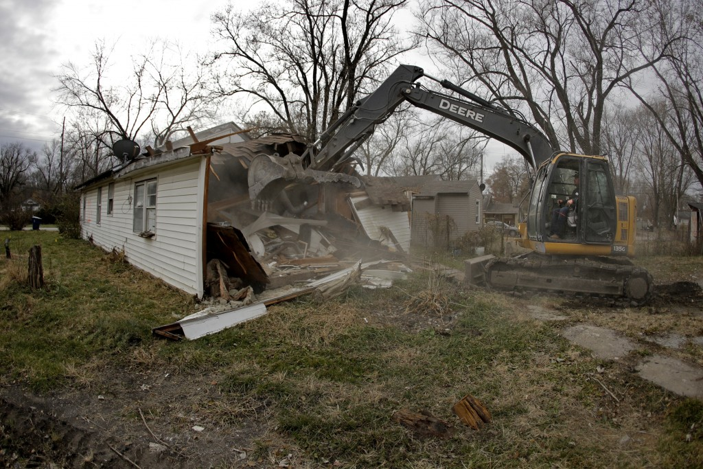 In this photo taken Monday, Nov. 18, 2019, Tim Kates demolishes Tammy Kilgore's former home as part of a voluntary buyout in flood-prone Mosby, Mo. Ki...
