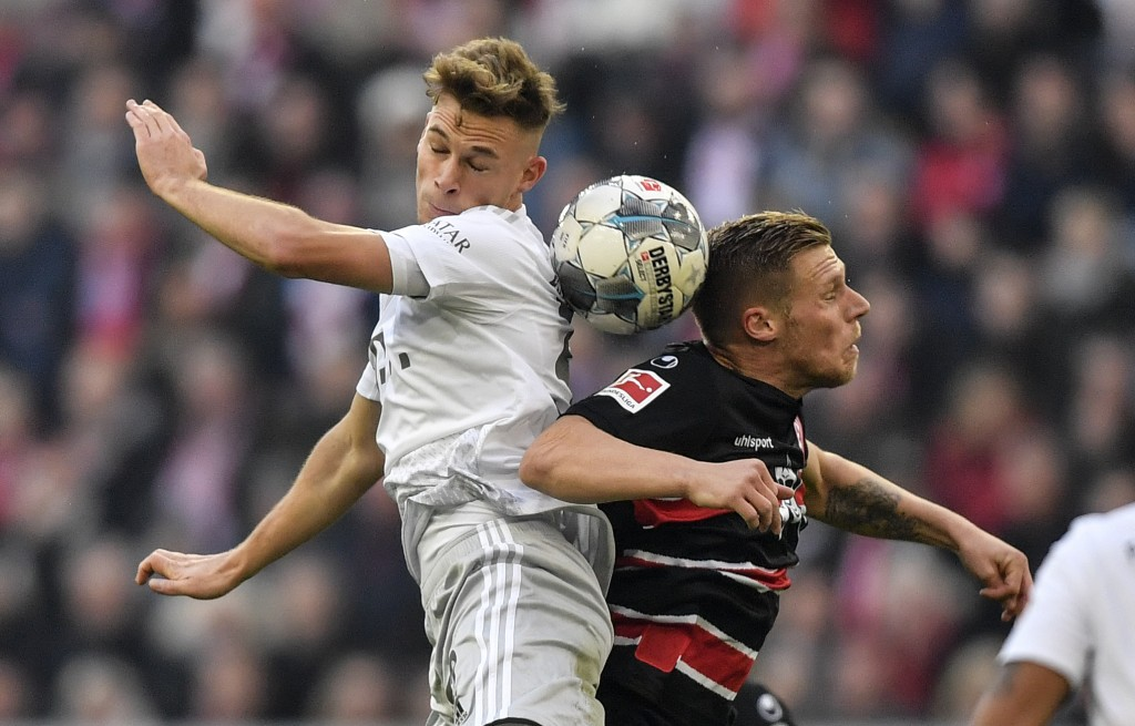 Bayern's Joshua Kimmich, left, and Duesseldorf's Rouwen Hennings challenge for the ball during the German Bundesliga soccer match between Fortuna Dues...