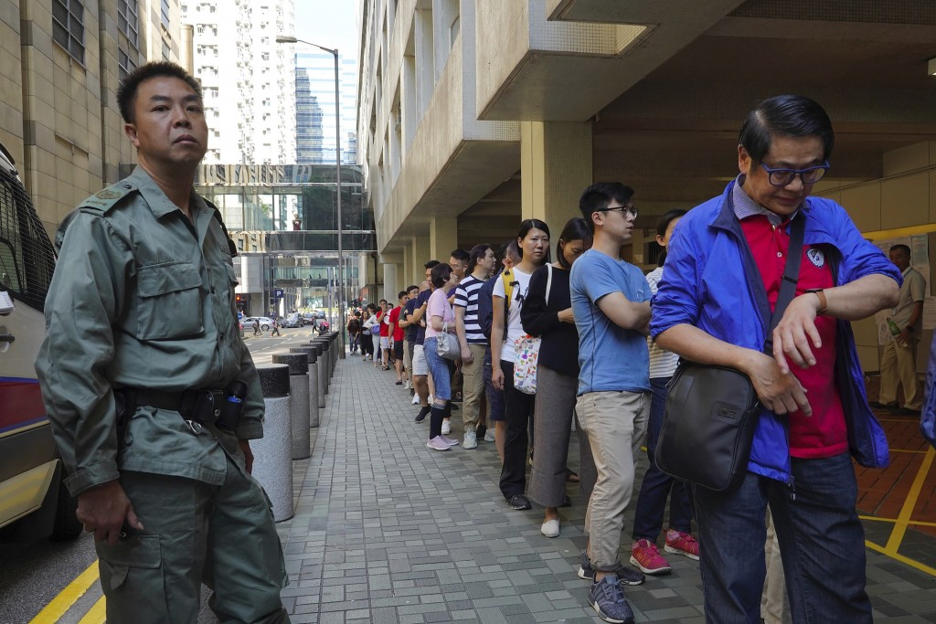 A policeman watches as people line up to vote outside of a polling place in Hong Kong, Sunday, Nov. 24, 2019. Long lines formed outside Hong Kong poll...