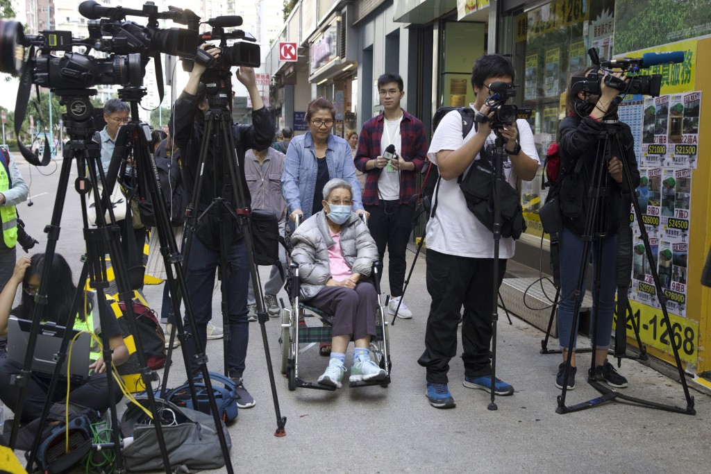 A woman in a wheelchair moves past journalists outside of a polling place in Hong Kong, Sunday, Nov. 24, 2019. Voting was underway Sunday in Hong Kong...