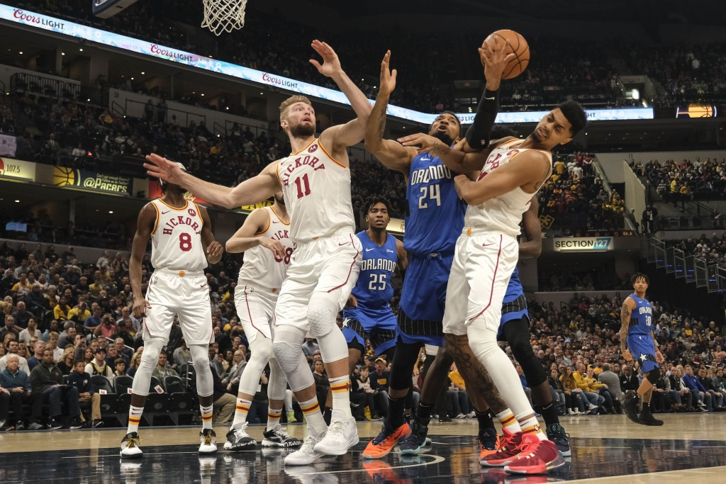 Orlando Magic center Khem Birch, center, battles for a rebound with Pacers forward Domantas Sabonis, left, and Jeremy Lamb during the first half of an...