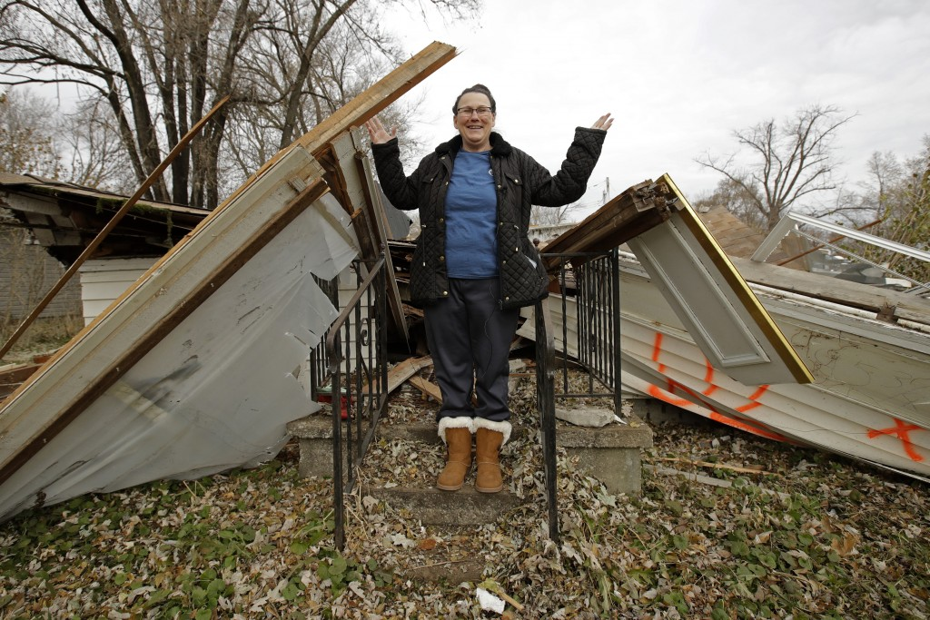 In this photo taken Monday, Nov. 18, 2019, Tammy Kilgore stands on the front porch of her home after it was demolished as part of a voluntary buyout i...