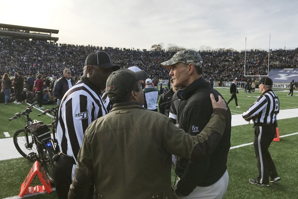Harvard coach Tim Murphy, right, gets an updated as demonstrators stage a protest on the field at the Yale Bowl disrupting the start of the second hal...
