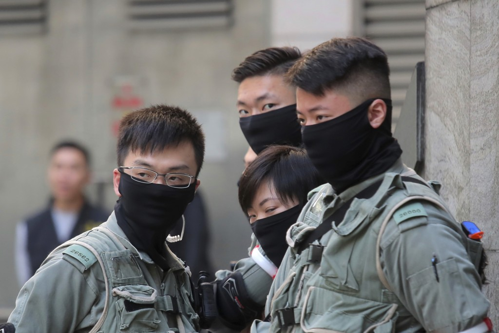 Riot police stand outside of a polling place in Hong Kong, Sunday, Nov. 24, 2019. Voting was underway Sunday in Hong Kong elections that have become a...