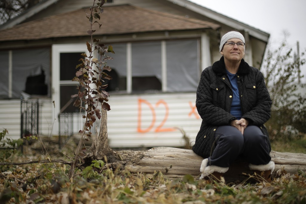 In this photo taken Monday, Nov. 18, 2019, Tammy Kilgore sits in front of her former home in Mosby, Mo. before it was demolished as part of a voluntar...