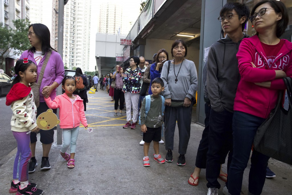 People line up to vote outside of a polling place in Hong Kong, Sunday, Nov. 24, 2019. Voting was underway Sunday in Hong Kong elections that have bec...
