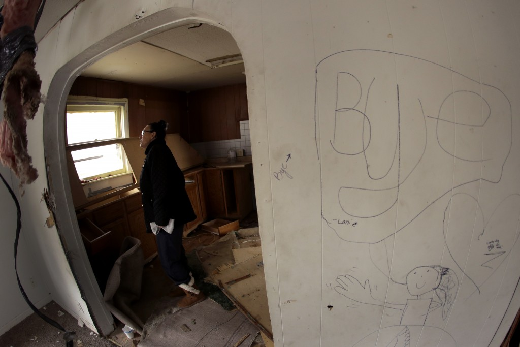 In this photo taken Monday, Nov. 18, 2019, Tammy Kilgore walks through her home for the final time before it was demolished as part of a voluntary buy...