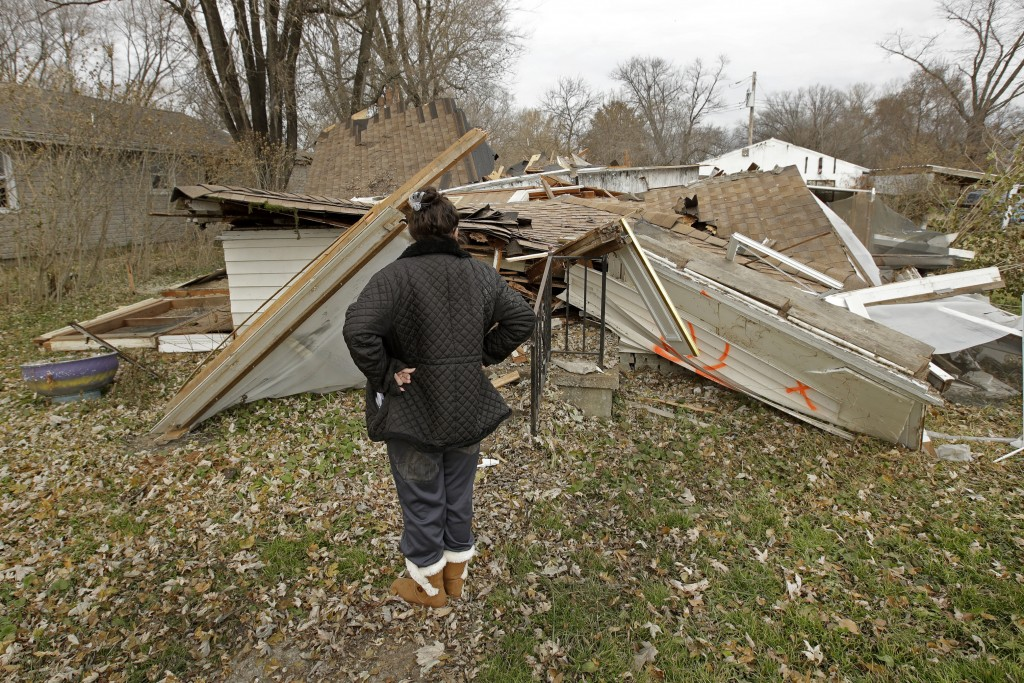 In this photo taken Monday, Nov. 18, 2019, Tammy Kilgore looks over the remains of her home after it was demolished as part of a voluntary buyout in f...