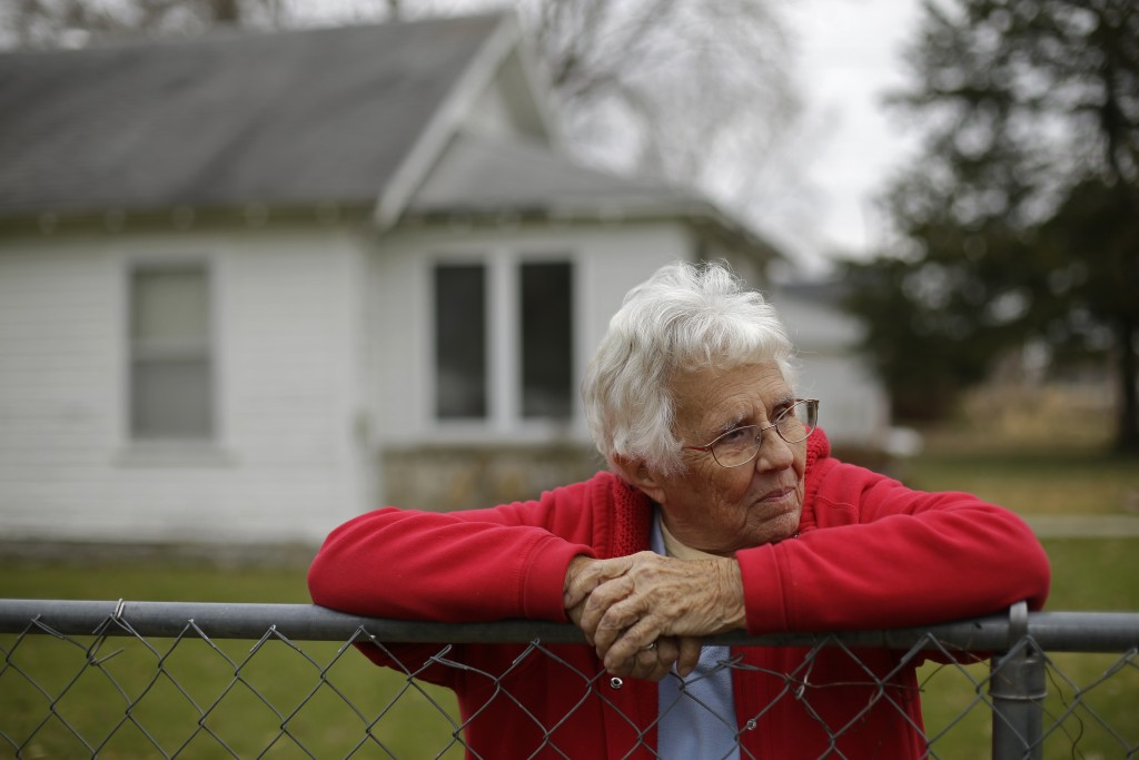 In this photo taken Monday, Nov. 18, 2019, Betty Cazzell watches from her adjacent fence line while her neighbor, Tammy Kilgore's home is demolished i...