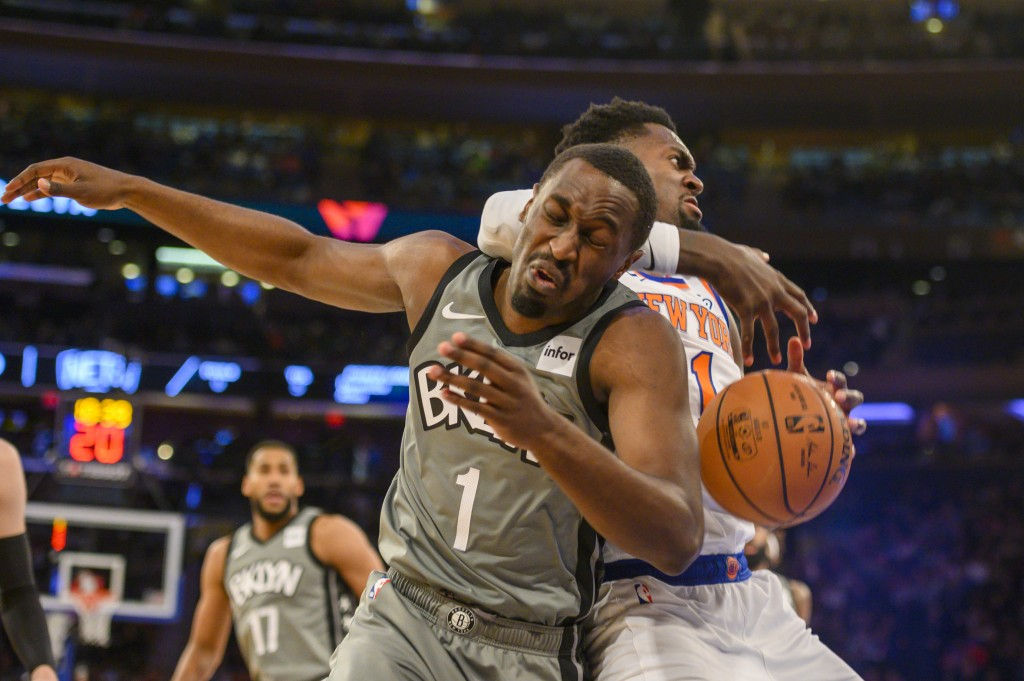 Brooklyn Nets guard Theo Pinson, front left, and New York Knicks forward Bobby Portis, right, fight for a rebound in the first half of an NBA basketba...