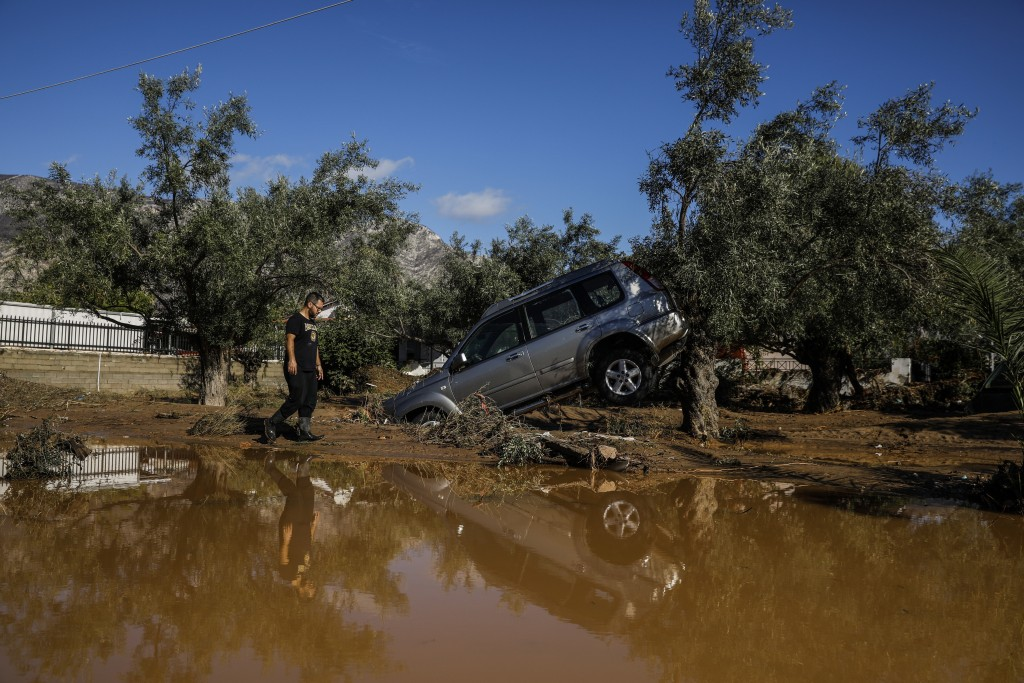 A man walks past a car moved by the force of flood water after storms in Kineta village, about 68 Kilometers (42 miles) west of Athens, Monday, Nov. 2...