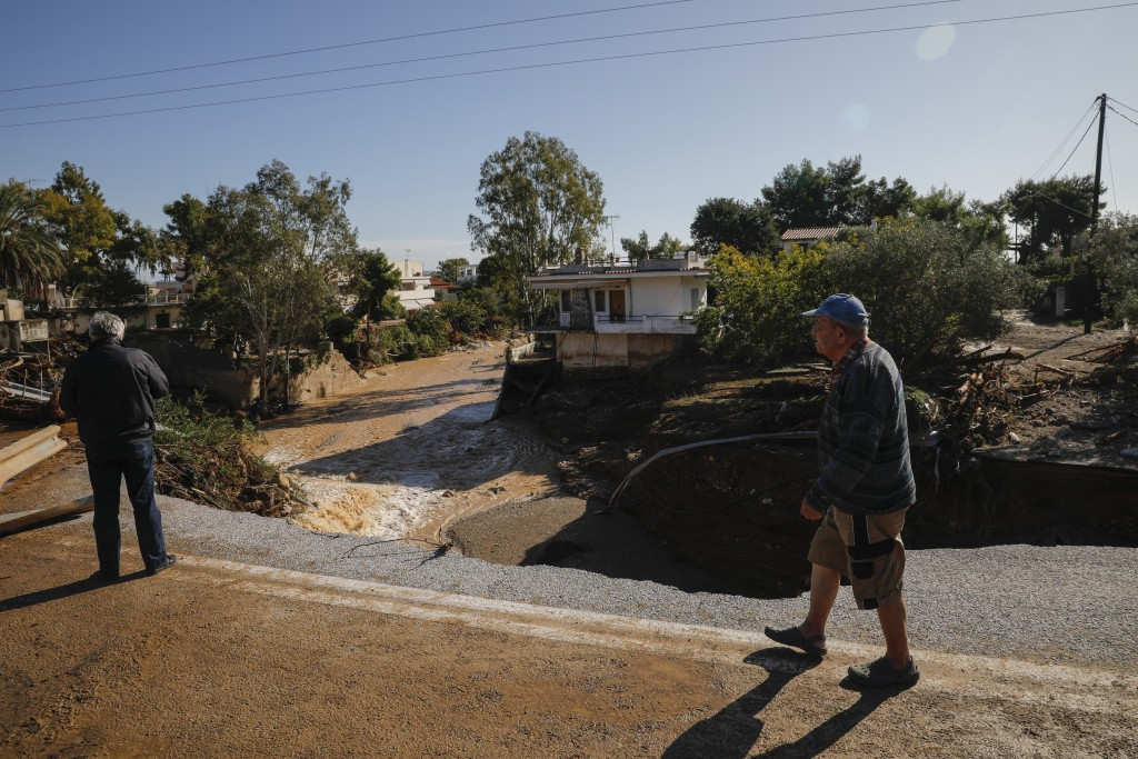 People inspect a damaged road after storms in Kineta village, about 68 kilometers (42 miles) west of Athens, Monday, Nov. 25, 2019. Authorities in Gre...