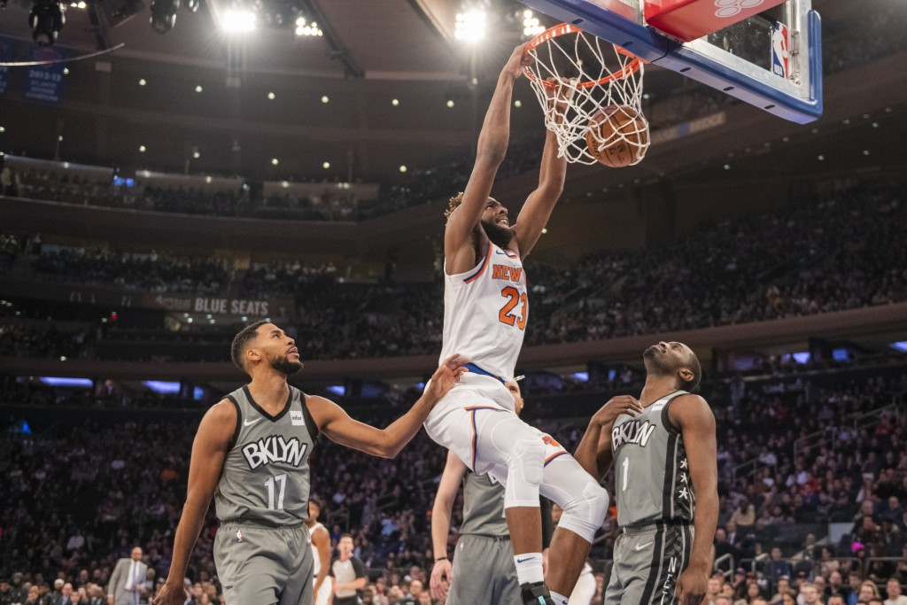 New York Knicks center Mitchell Robinson (23) dunks over Brooklyn Nets guards Garrett Temple (17) and Theo Pinson (1) in the first half of an NBA bask...