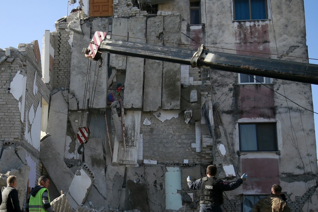 Rescuers search at a damaged building after a magnitude 6.4 earthquake in Thumane, western Albania, Tuesday, Nov. 26, 2019. Rescue crews used excavato...