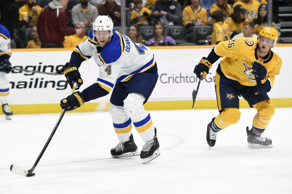 St. Louis Blues defenseman Carl Gunnarsson (4), of Sweden, passes the puck in front of Nashville Predators left wing Daniel Carr (26) during the secon...