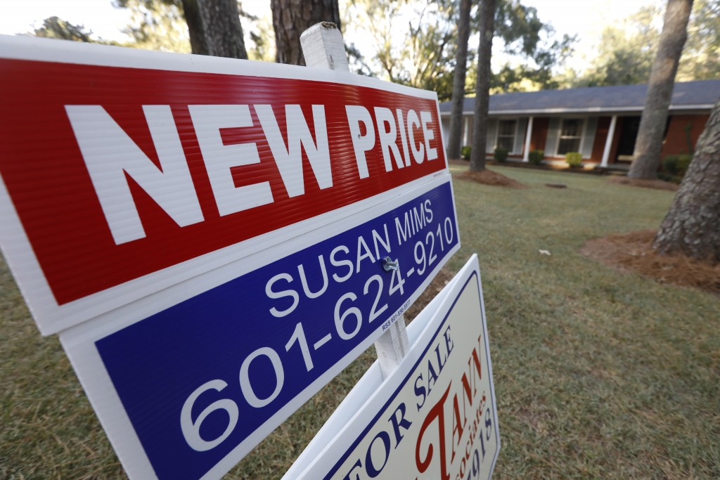 FILE - In this Sept. 25, 2019, file photo a sign indicating a new selling price for a house sits atop a realtor's sign in Jackson, Miss. On Tuesday, N...