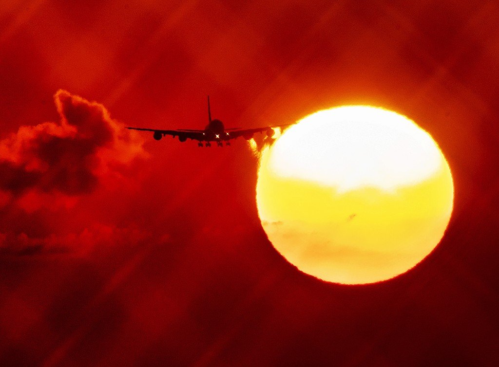 FILE - In this Wednesday, Aug. 21, 2019 file photo, an aircraft passes the rising sun as it approaches the airport in Frankfurt, Germany. The European...