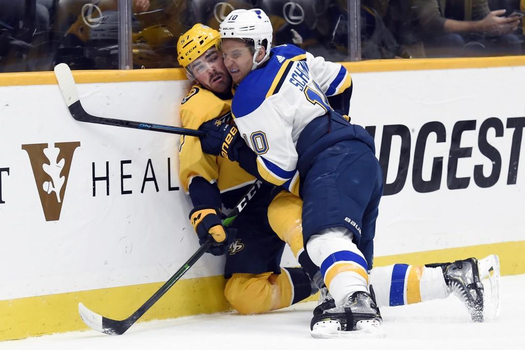 St. Louis Blues center Brayden Schenn (10) checks Nashville Predators defenseman Dante Fabbro (57) into the boards during the first period of an NHL h...