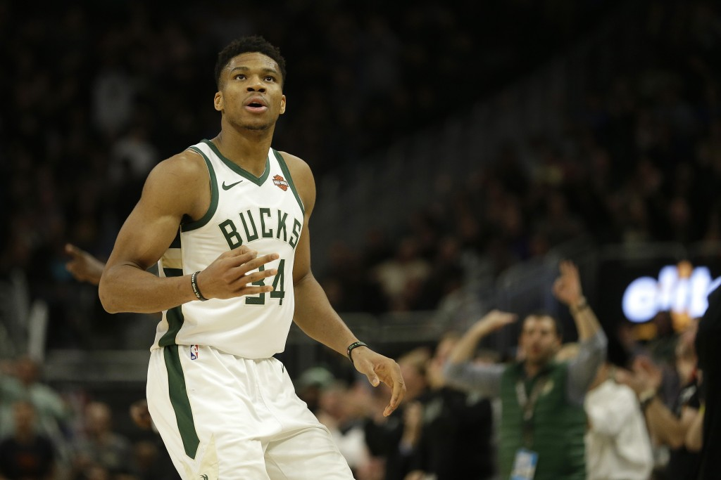 Milwaukee Bucks' Giannis Antetokounmpo reacts after making a 3-pointer during the second half of an NBA basketball game against the Utah Jazz Monday, ...