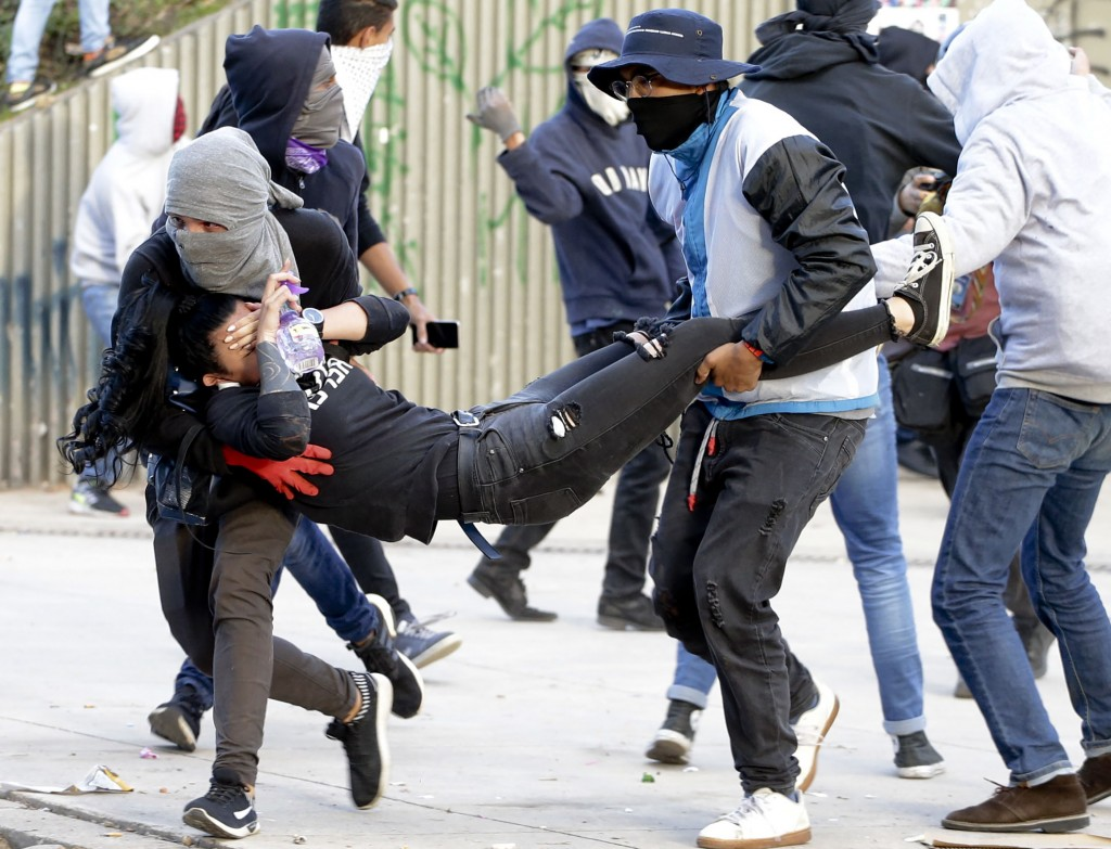 Students carry a youth injured curing clashes with police at the National University in Bogota, Colombia, Tuesday, Nov. 26, 2019. Protesters are calli...