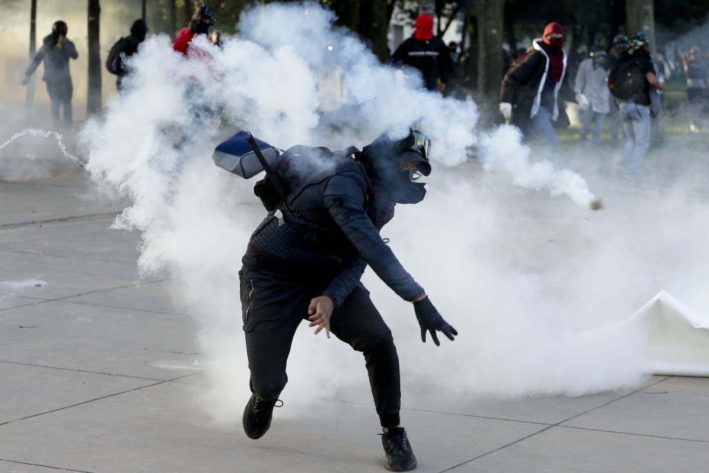 A student throws a tear gas canister back at the police during clashes at the National University in Bogota, Colombia, Tuesday, Nov. 26, 2019. Protest...