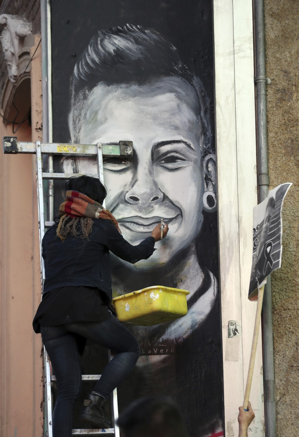 A demonstrator paints a mural with the likeness of Dilan Cruz who was injured during clashes between anti-government protesters and police, during a m...