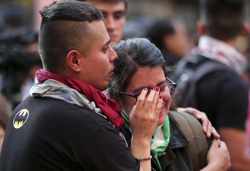 A young woman is comforted by a fellow demonstrator during a protest for Dilan Cruz who was injured during clashes between anti-government protesters ...