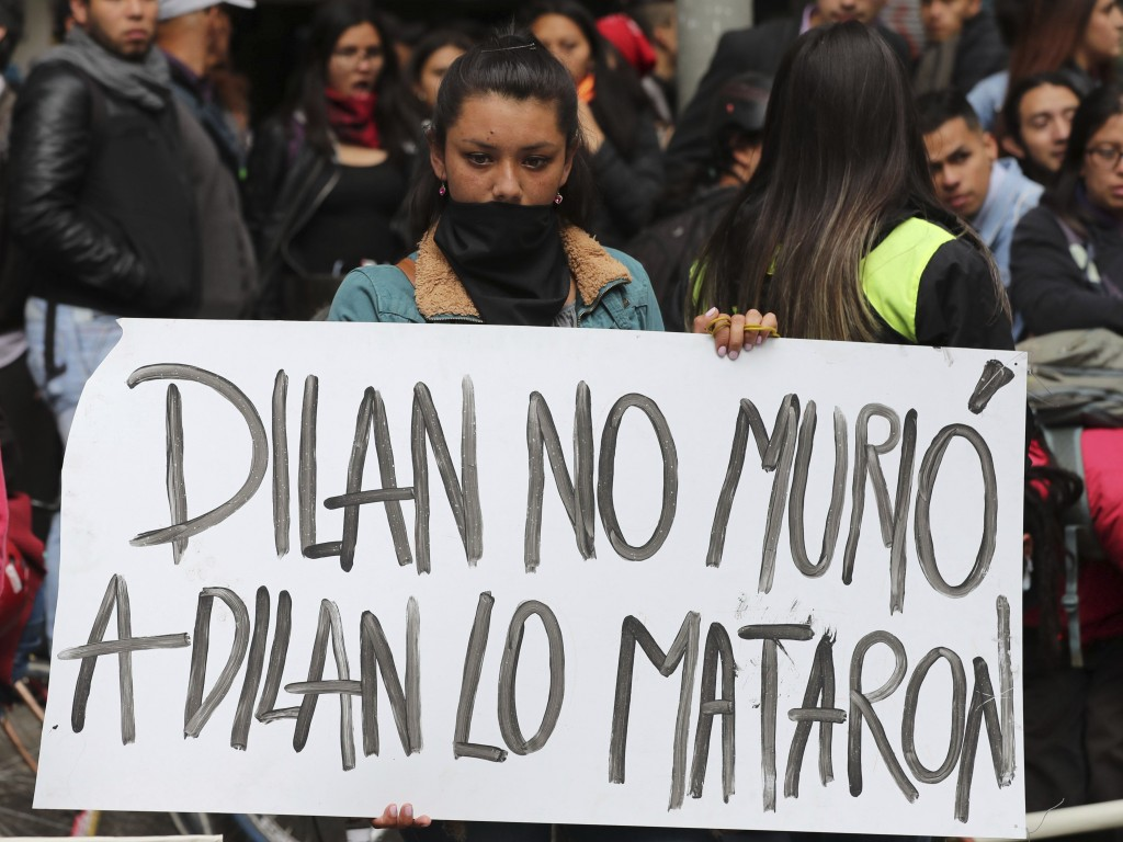 """A woman holds a sign that reads in Spanish """"Dilan did not die. Dilan was murdered"""" in reference to Dilan Cruz who was injured during clashes between a..."""