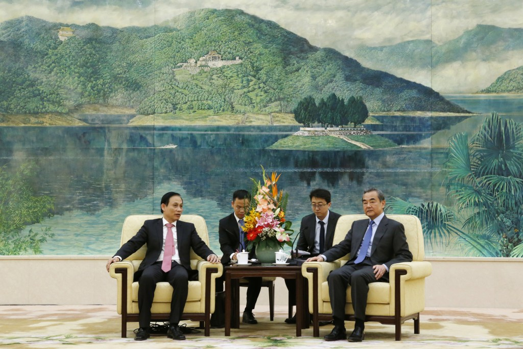 FILE - In this Nov. 27, 2019, file photo, Vietnam's Deputy Foreign Minister Le Hoai Trung, left, attends a meeting with Chinese Foreign Minister Wang ...