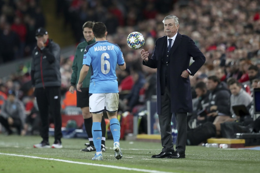 Napoli's head coach Carlo Ancelotti throws the ball to Napoli's Mario Rui, 6, during the Champions League Group E soccer match between Liverpool and N...