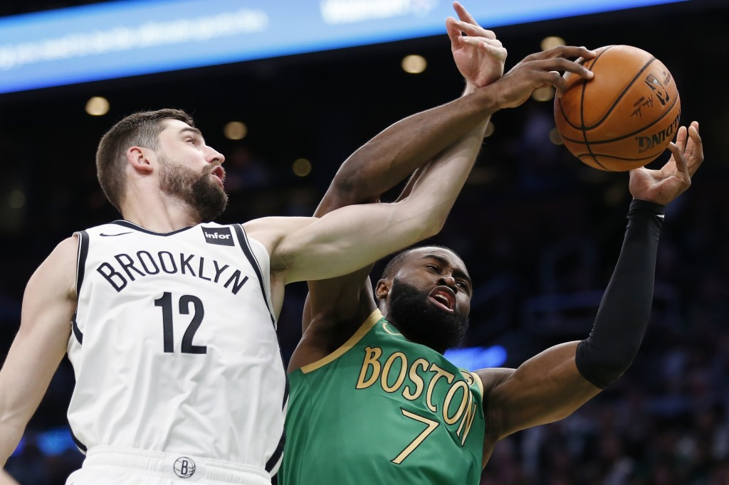 Boston Celtics' Jaylen Brown (7) and Brooklyn Nets' Joe Harris (12) reach for a rebound during the first half of an NBA basketball game in Boston, Wed...