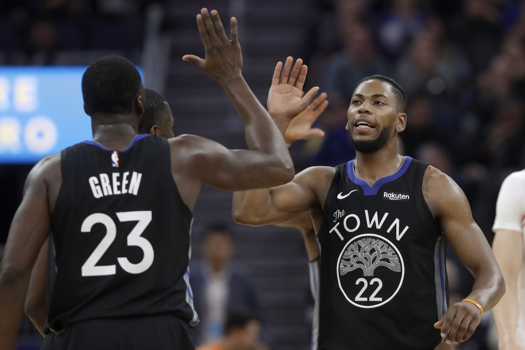 Golden State Warriors forward Glenn Robinson III (22) celebrates with forward Draymond Green (23) during the first half of the team's NBA basketball g...