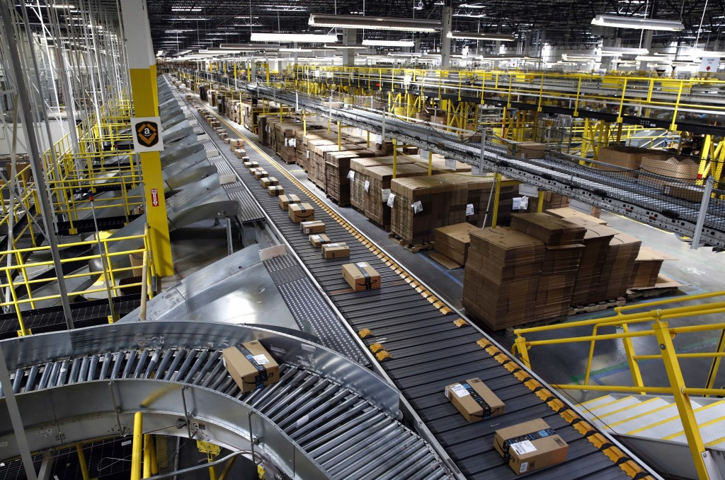 FILE- In this Aug. 3, 2017, file photo, packages ride on a conveyor system at an Amazon fulfillment center in Baltimore. Amazon, Walmart and others ar...