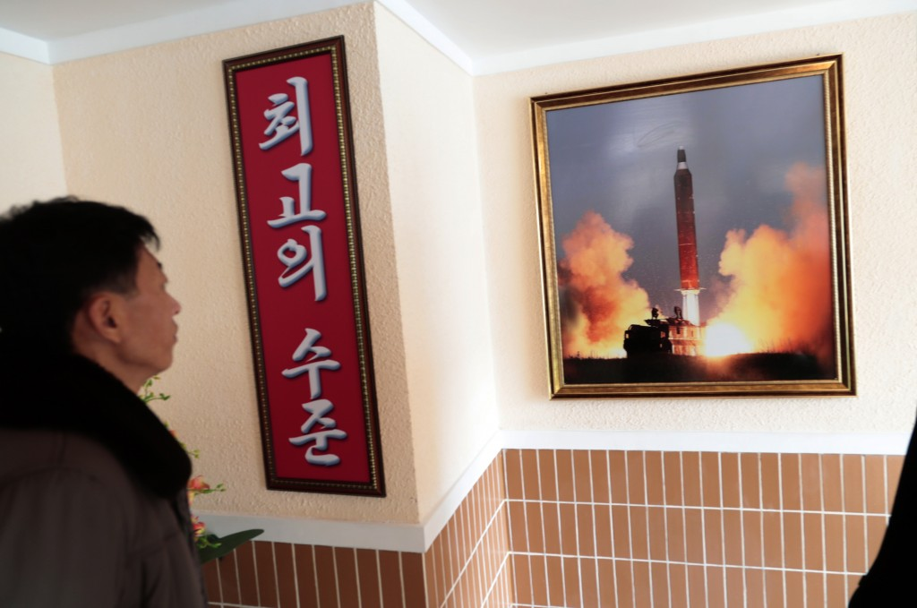 In this Nov. 26, 2019, photo, a man looks at a photo of the launch of a missile hanging on the wall of a factory workers' dormitory in Pyongyang, Nort...