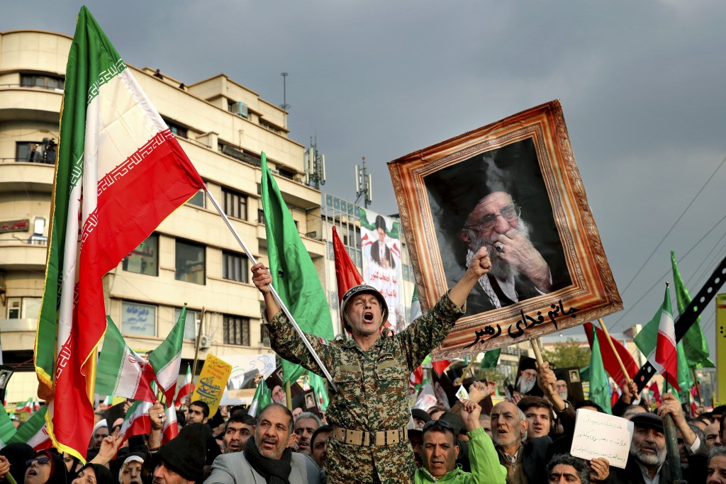 FILE - In a Nov. 25, 2019, file photo, a demonstrator chants slogans while holding up an Iranian national flag during a pro-government rally in Tehran...