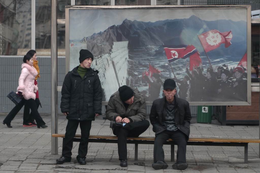 In this Nov. 26, 2019, photo, men wait for public transport near a propaganda photo showing North Korean 'soldiers-builders' in downtown Pyongyang, No...